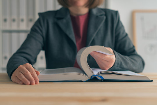 Businesswoman reading book at office desk
