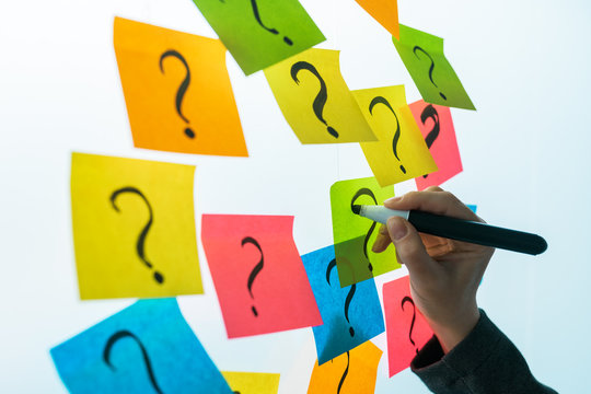 Businesswoman writing question marks on colorful sticky note paper