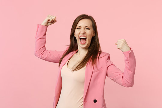 Portrait of overjoyed screaming young woman in jacket clenching fists like winner isolated on pastel pink wall background in studio. People sincere emotions, lifestyle concept. Mock up copy space.