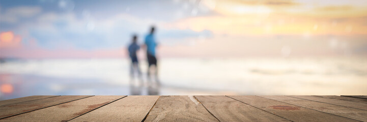 empty wood table on blurred of people walk on the beach with sunrise, warm tone