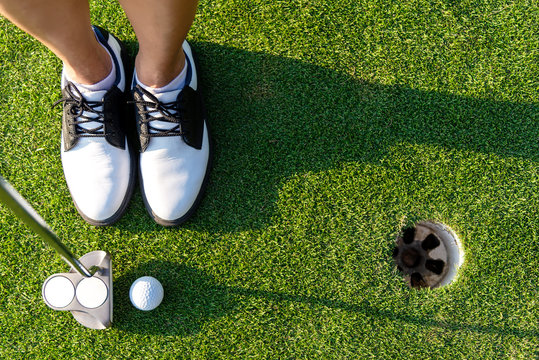 Top View golfer asian sporty woman focus putting golf ball on the green golf.  Healthy and Lifestyle Concept