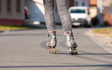 Female legs with inline roller skates. Asphalt road in the town with cars and buildings.