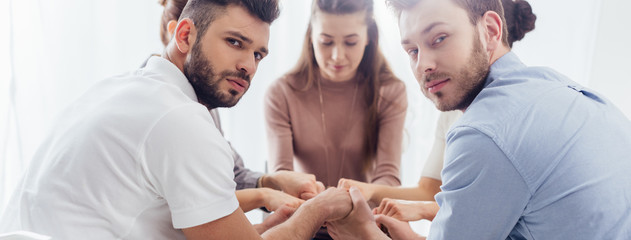 panoramic shot of group of people sitting and stacking hands during therapy session