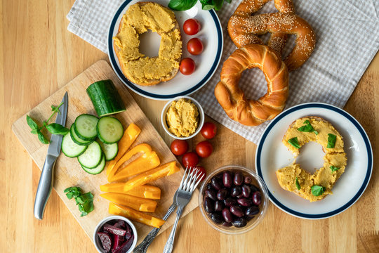 Vegan breakfast with home baked bagels with spread hummus and herbs, slices of cucumber, yellow peppers, cherry tomatoes, olives and grapes as dessert. Healthy food flat lay. Eating well concept.