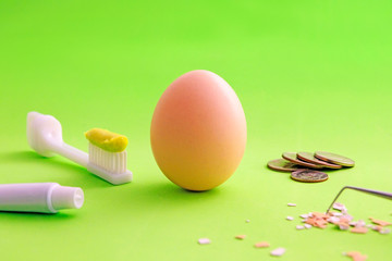 Egg, toothbrush, tube of toothpaste. Coins, eggshell, dental instrument. Creative concept of oral hygiene or dental care. The concept of dentistry. How to Protect teeth?