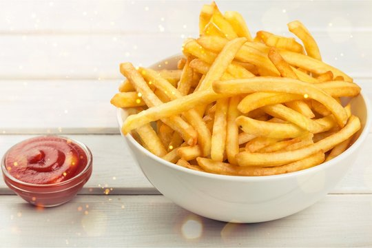 Paper box with pile of appetizing french fries over white planks background