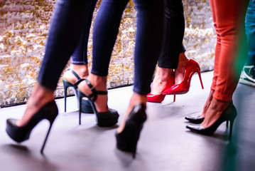 Close up of four women's legs in high heels at the disco. Three high heels shoes are black and one red Fototapete