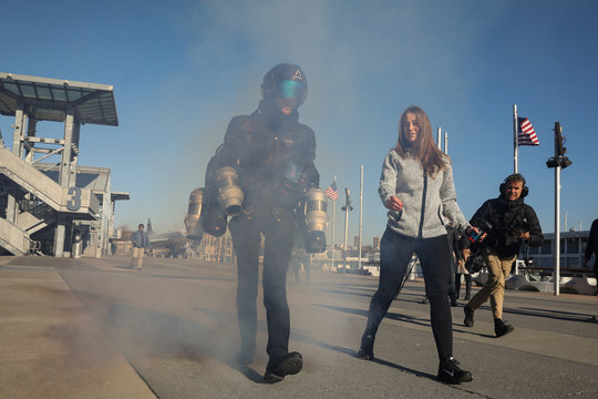 Sam Rogers, flight suit design engineer at Gravity Industries, walks in a cloud of smoke after demonstrating a Jet Suit at the Intrepid Sea, Air & Space Museum in New York