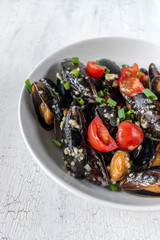 Seafood dish of cooked mussels with garlic, tomatoes, and green onions
