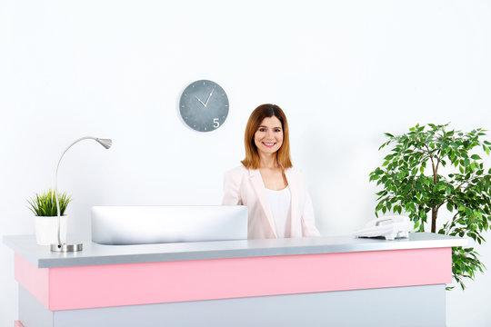 Beautiful woman working at reception desk in beauty salon