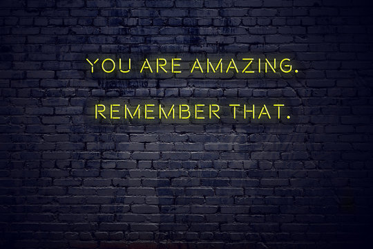 Positive inspiring quote on neon sign against brick wall you are amazing remember that