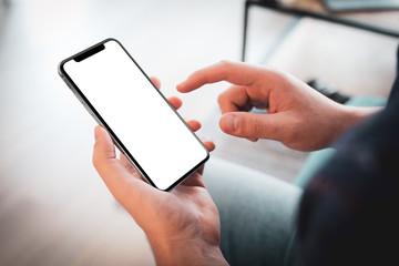 Man hand holding black smartphone blank screen, modern frame less design in home interior, living room - angled position