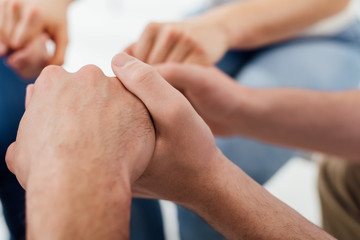 cropped view of men holding hands during group therapy session