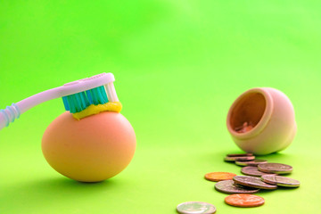 Toothbrush with toothpaste is on the whole egg. A symbol of the strength of the teeth. Oral hygiene. Next to the barrel scattered metal money - coins, cents. Healthy teeth concept. Green background.