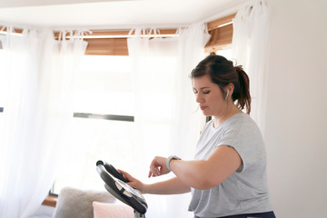 Woman checking time while exercising on stationary bicycle