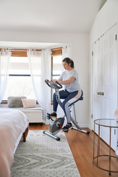 Woman exercising on stationary bicycle