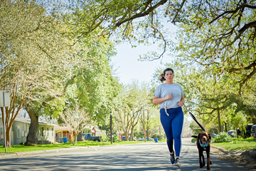 Woman with dog running on road