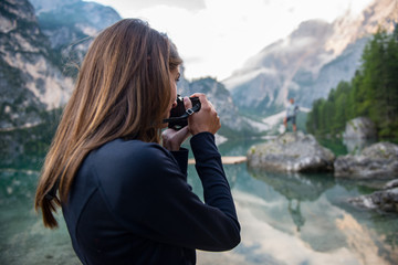 Brunette woman taking picture of man with camera