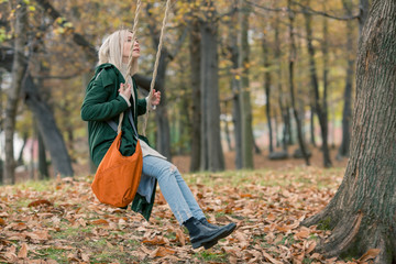 Young woman with bleached hair swinging on swing in forest