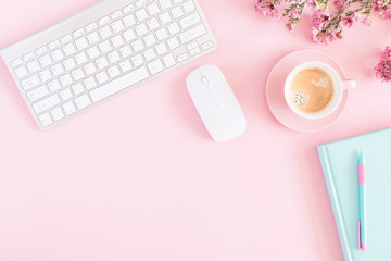 Office pink table, notepad, keyboard, flowers, coffee, notebook, stationery on pink background....