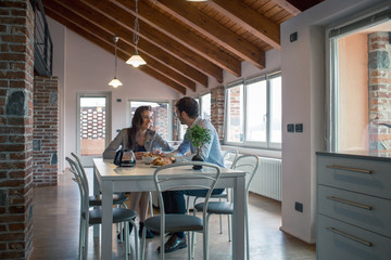 Smiling couple sitting at dining table at home