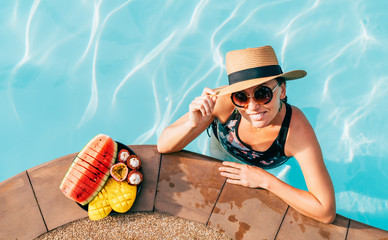 Smiling woman in straw hat in sunglasses swimming in pool and enjoying fresh tropical fruits