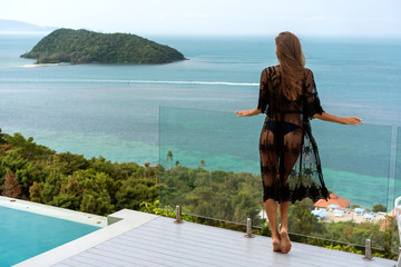 girl stands on the seashore overlooking the mountains near the pool