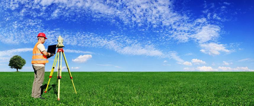 Surveyor on green field