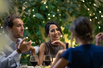 Young couples having dinner at table