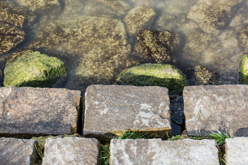 Stones on shore next to river