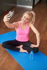 Young attractive sporty woman sitting on yoga mat making selfie with her mobile phone