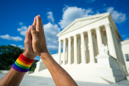 Gay pride hands held together in beseeching gesture in front of US Supreme Court building in Washington DC