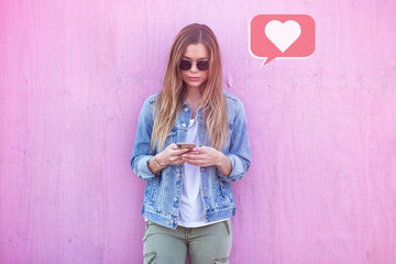 Beauty Girl Influencer Using Social Media on Smartphone with Like icon Around on Pink Background Wall mural
