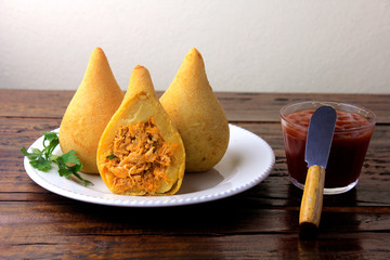 Coxinha in the dish, traditional Brazilian cuisine snacks stuffed with chicken, on rustic wooden table