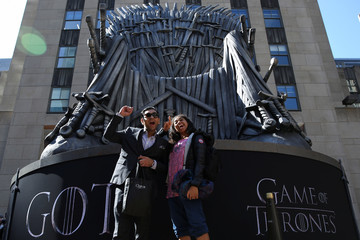 "Fans take pictures in front of a large replica of the iron throne before the premiere of the final season of ""Game of Thrones"" at Radio City Music Hall in New York"