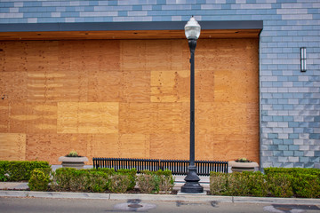 Plywood shutters prevent unauthorized access by squatters, looters or vandals to unused, vacant, or abandoned property. Economic recession concept - bankrupt business boarded up with plywood sheets