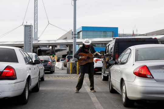 A man plays the guitar as cars queue up in multiple lines  waiting to be inspected by U.S. border patrol officers to enter from Mexico into the U.S., at the San Ysidro port of entry, in Tijuana