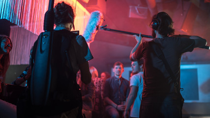 Cameraman and director with a film camera on a film set in a club with red light. Wall mural
