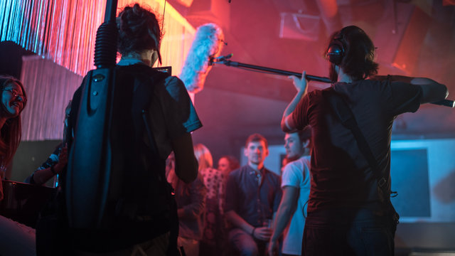 Cameraman and director with a film camera on a film set in a club with red light.