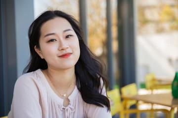 Smiling pensive Asian girl relaxing in outdoor coffee shop
