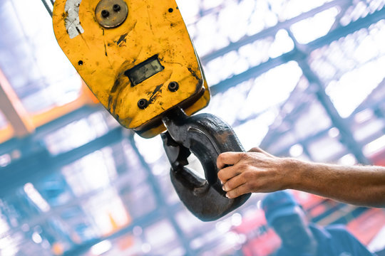 Industrial crane hook being guided by engineers hand