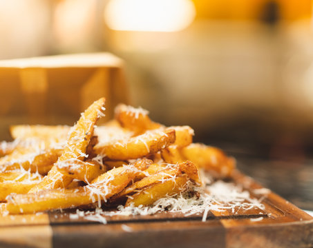 delicious homemade fried potato with shredded cheese on wooden plate, nice snack presentation for restaurant
