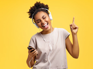 Cheerful young girl in headphones, dance actively. Photo of african american girl wears casual outfit on yellow background. Emotions and pleasant feelings concept.