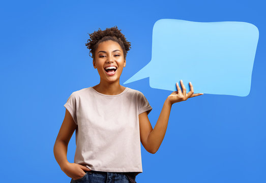 Happy laughing girl holds blue speech bubble banner. Photo of african american girl wears casual outfit on blue background. Emotions and pleasant feelings concept.