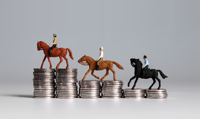Miniature men riding horse on coin stacks.