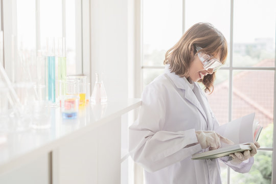 A young Asian woman scientist reading a book in laboratory with test tube microscope and solutions.