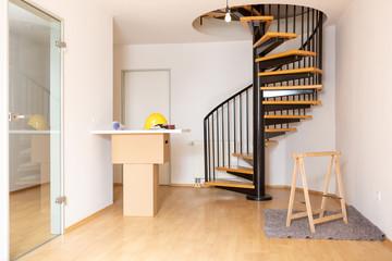 Ein Planungstisch für den Bauherren mit Bauplan und Helm in einer leeren Maisonette Wohnung