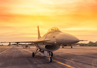 Fighter jet military aircraft parked on runway in the base airforce standby ready to take off for military mission on sunset