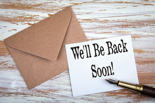 We'll Be Back Soon. Paper letter and pen on a wooden table