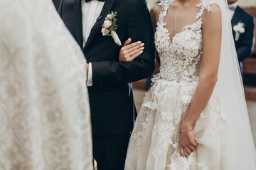 luxury wedding couple hugging, holding hands during traditional wedding ceremony in church. priest blessing them. space for text. spiritual stylish bride and groom